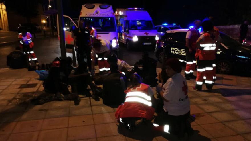 Miembros de Cruz Roja atienden a un inmigrante tras saltar la valla en Ceuta