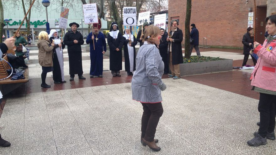 Simulación de escolares en el patio escolar frente a un grupo de religiosos que les arrastran hasta la clase de religión.