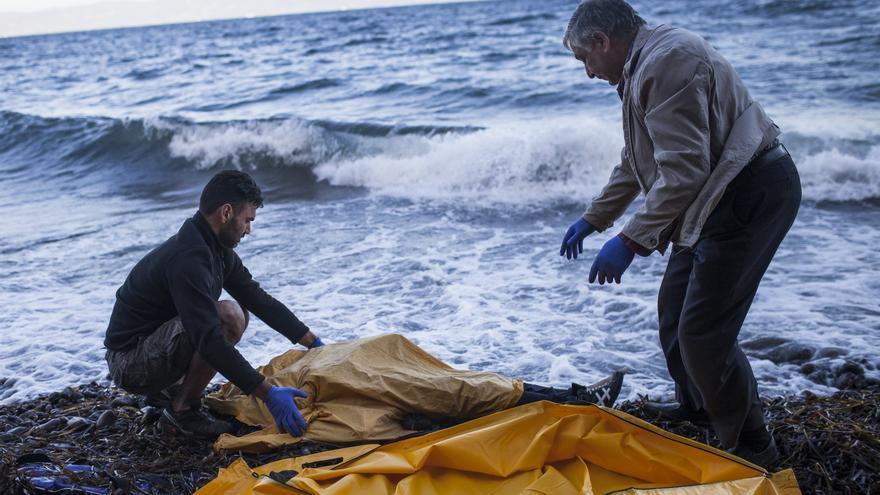 Dos personas a punto de trasladar el cadáver de un refugiado en Lesbos, Grecia, tras los múltiples naufragios de estos días