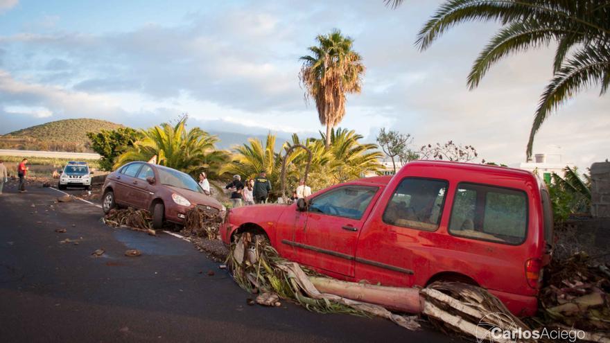 En la imagen, dos vehículos arrastrados por la avenida de agua. Foto: CARLOS ACIEGO.