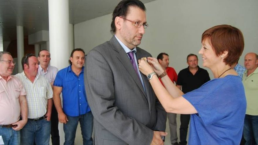 Pilar Martín, acusada en este juicio, coloca la insignia al presidente que le daba el relevo en el Consejo, Eugenio García