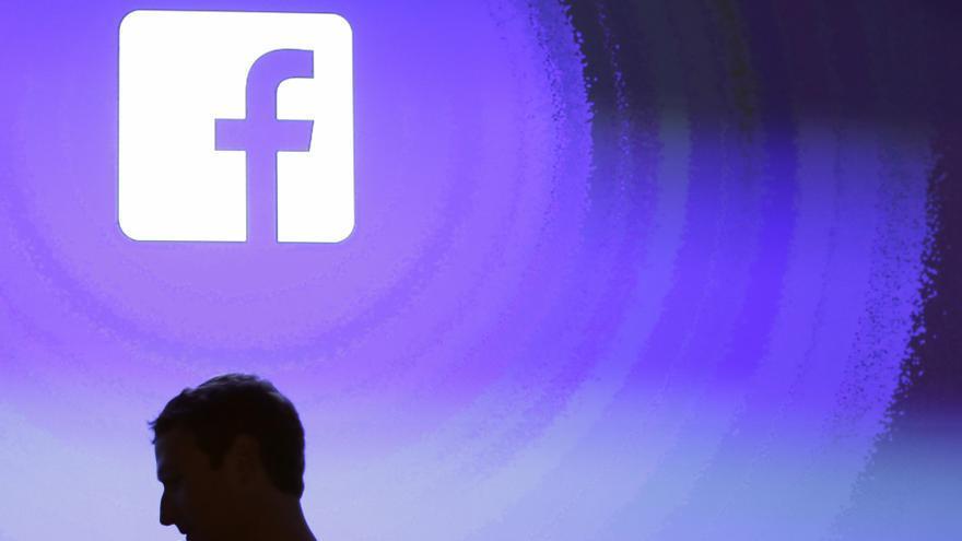 Mark Zuckerberg pasa por delante de un logo de Facebook en Menlo Park, la sede de la compañía en EEUU.