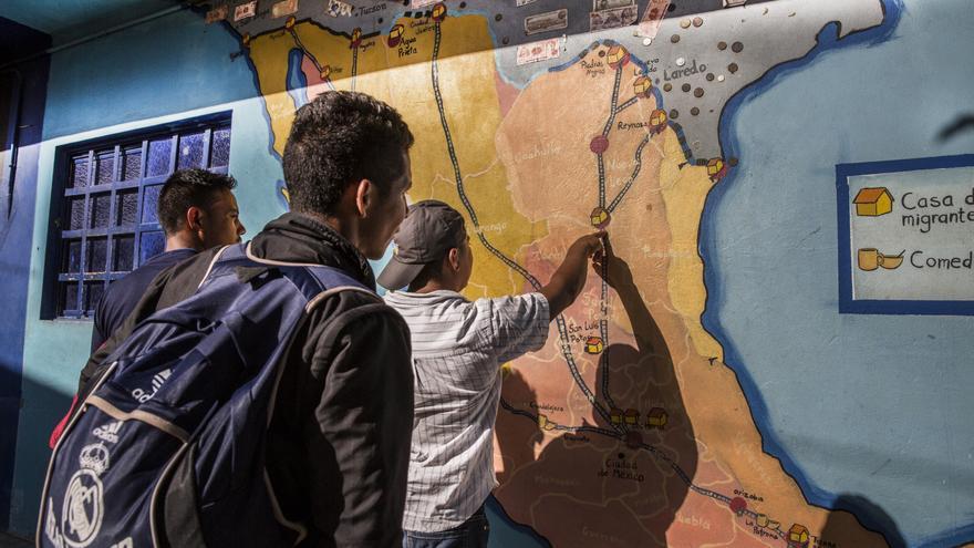 Varias personas consultan la ruta en un mapa de México pintado en los muros del albergue.