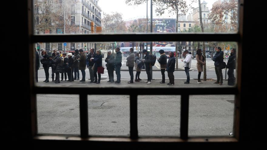 Numerosos ciudadanos guardan cola en el colegio electoral de la Plaza de la Universidad de la ciudad condal. EFE/Javier Etxezarreta