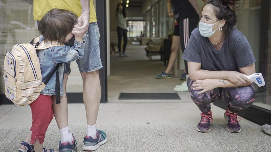 En la entrada de la escuela infantil La Llum, una educadora toma la temperatura de los niños y niñas