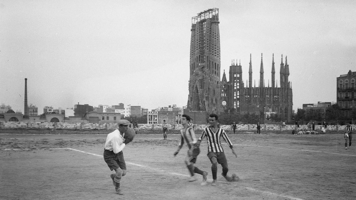 Es 1915 y se juega un partido de fútbol en el campo del Club Deportivo Europa, delante de la Sagrada Familia de Gaudí. Frederic Juandó Alegret.