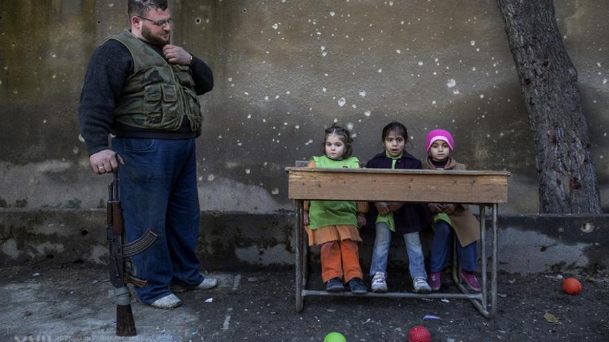 Los niños se sientan en los bancos de la clase en la escuela Al-Tawhid en Aleppo. La mayoría de las escuelas de Aleppo están cerradas. Debido a la falta de calefacción y electricidad, algunas clases se trasladan afuera./Niclas Hammarström.