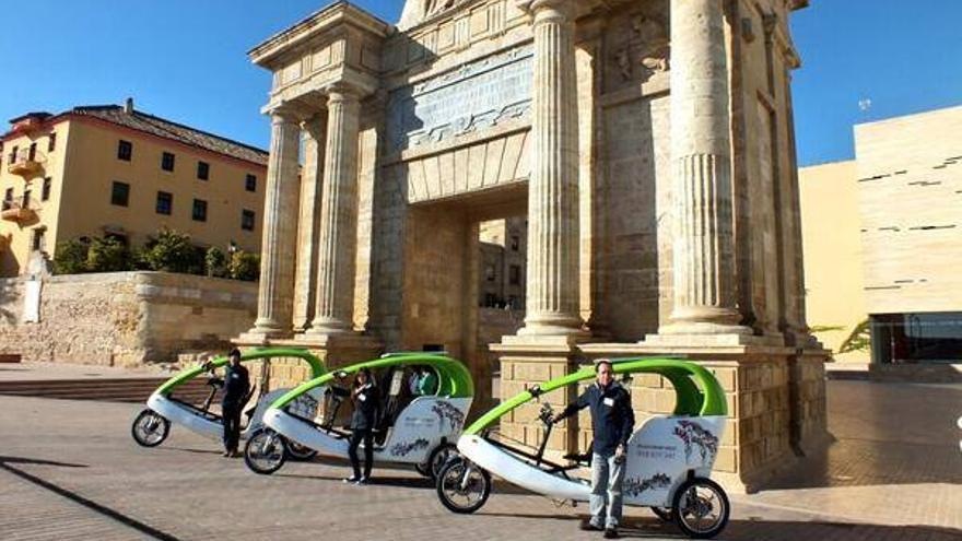 Triciclos solares turísticos de la empresa LuBan en la Puerta del Puente en Córdoba.