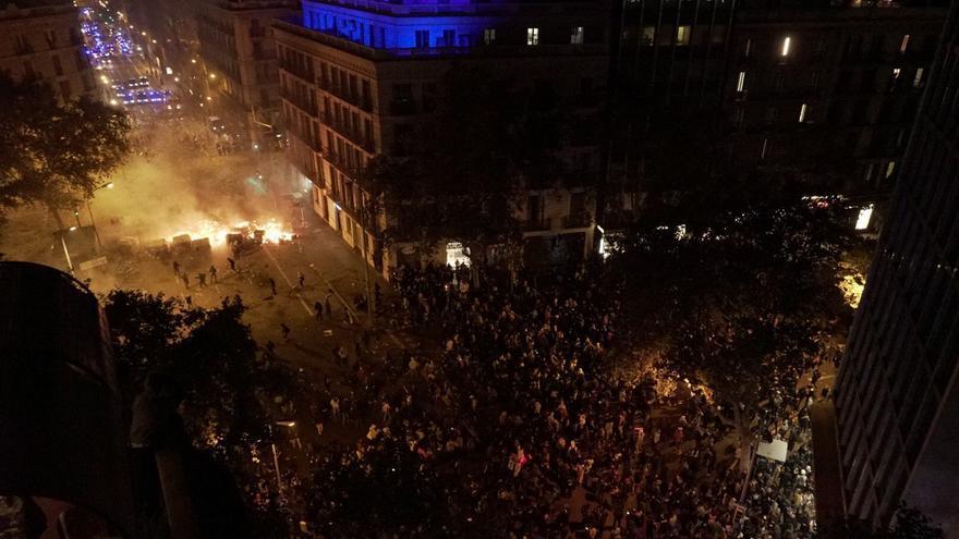 Una barricada separa a manifestantes y policías entre Pau Claris con Ronda Sant Pere en la quinta noche de protestas.