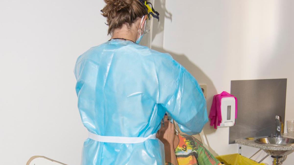 Una enfermera practica una test de Covid a una paciente.