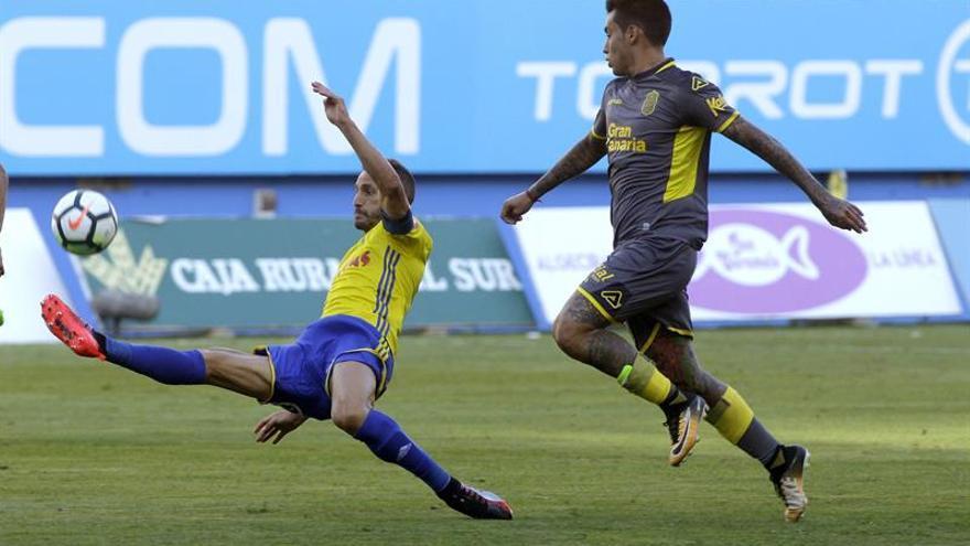 El defensa del Cádiz. Servando Sánchez lucha por el balón con el delantero de UD Las Palmas Sergio Araujo. (EFE/Román Ríos.)
