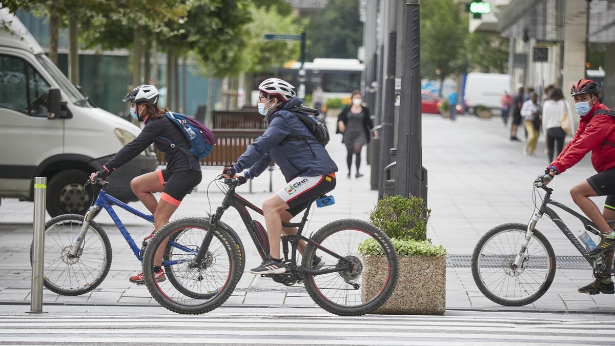 Personas en bici y con mascarilla en una céntrica calle de Pamplona.