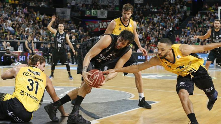 El jugador del Retabet Bilbao Basket Alex Mumbrú (c) disputa un balón con el jugador del Iberostar Tenerife Davin White (d) en el partido correspondiente a la liga Endesa disputado en el BilbaoArena. EFE/Luis Tejido