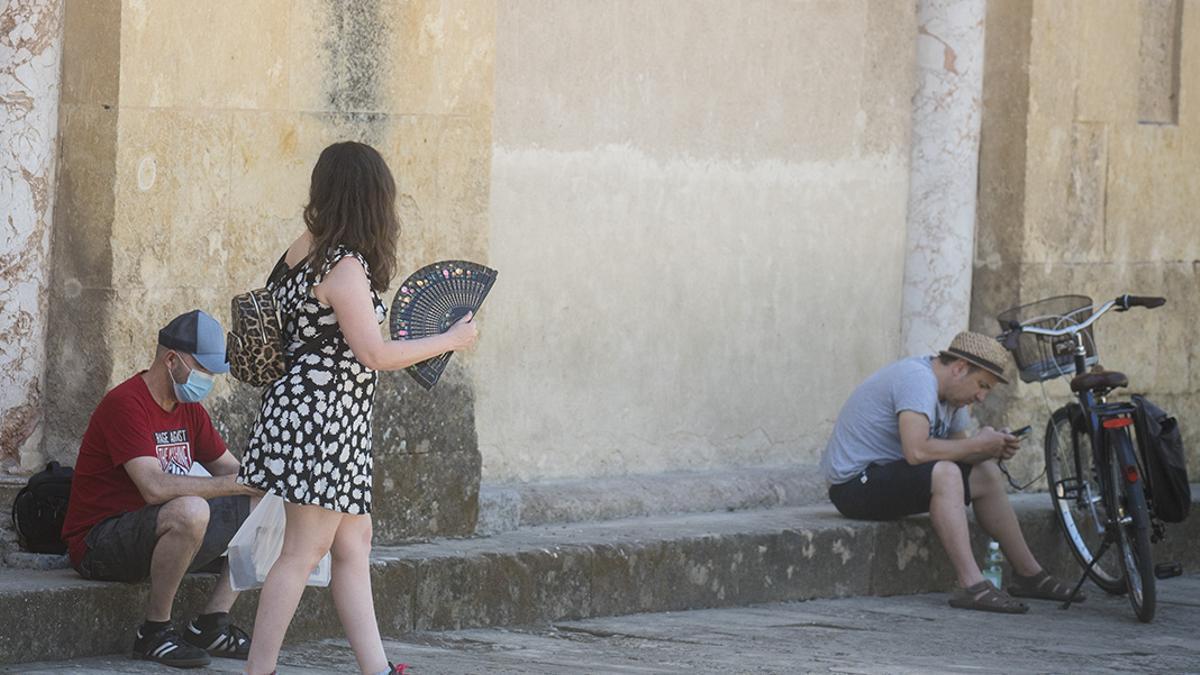 Una turista se abanica junto a la Mezquita