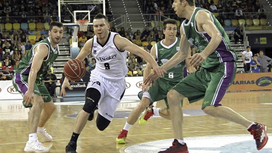 El escolta letón del Bilbao Basket, Dairis Bertans (c), inicia una entrada a canasta ante la oposición del pívot del Unicaja, Fran Vázquez (d), durante el partido de cuartos de final de la Cop del Rey de Baloncesto. (EFE/Ángel Medina G.).