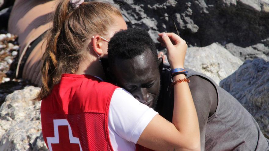 Una voluntaria de Cruz Roja sostiene a un migrante el martes en la playa de Ceuta.