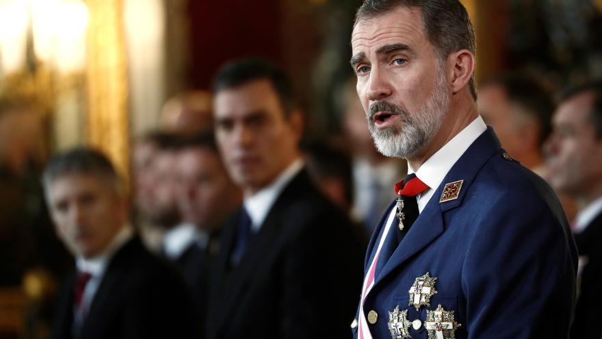 El rey Felipe VI pronuncia su discurso en presencia del presidente del gobierno en funciones Pedro Sánchez (2i), y el ministro del Interior en funciones Fernando Grande Marlaska (i), durante la Pascua Militar en una solemne ceremonia celebrada hoy en el Palacio Real de Madrid.