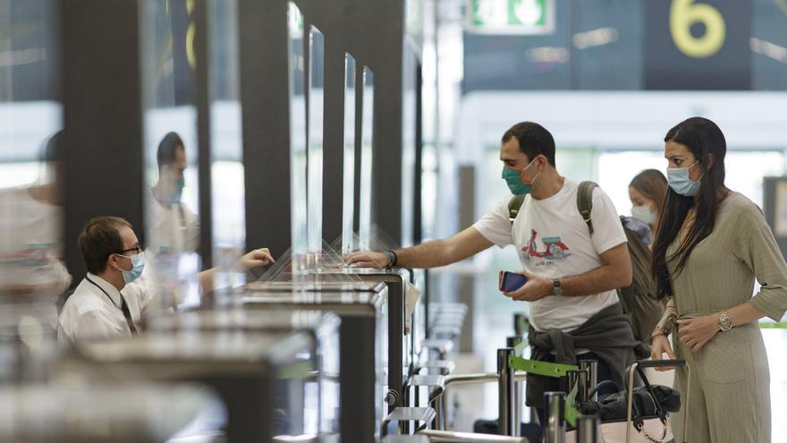 Dos pasajeros en el control de billetes de la terminal T4 del aeropuerto Adolfo Suárez Madrid-Barajas.
