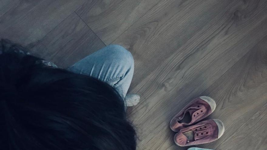 Imagen de Amaia (nombre ficticio) con los zapatos de sus dos hijos
