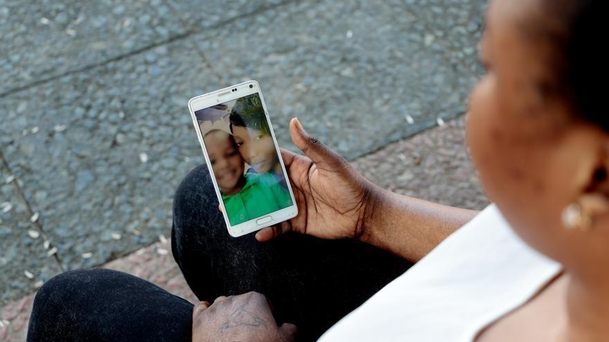 Oumo mira una foto en la que aparece con su hijo | Laura Martínez/ Women's Link