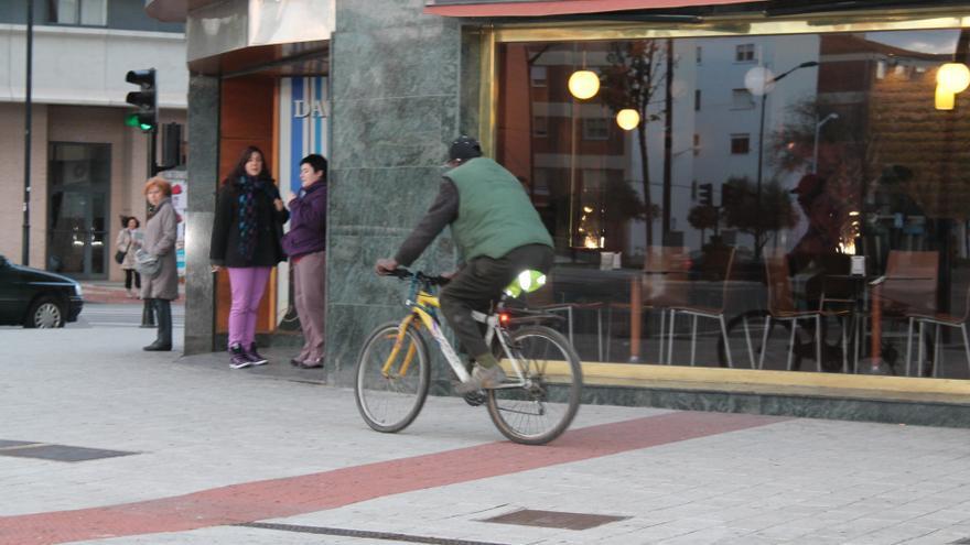 Un ciudadano recorre la ciudad andando en bicicleta por la acera. /EFE