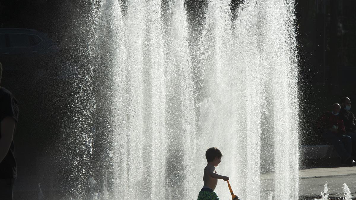 Un niño juega en el agua de una fuente en Montreal para refrescarse del calor.