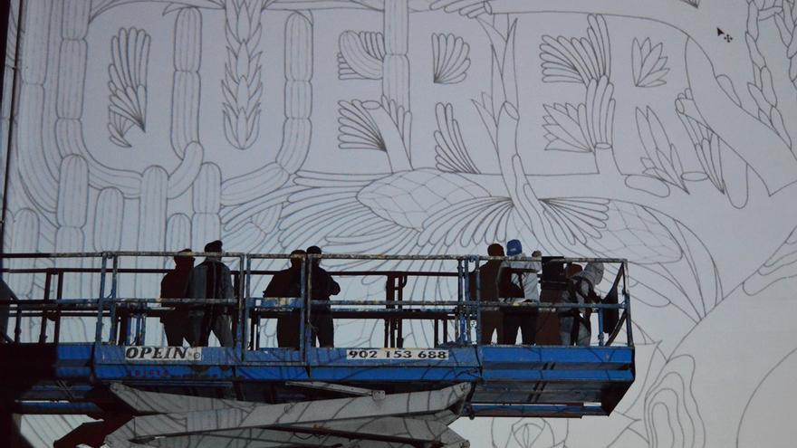 En la imagen, los miembros del colectivo realizando el grafitti.