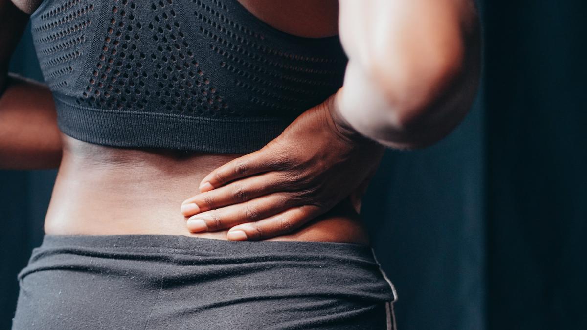 Una mujer se toca la parte baja de la espalda.