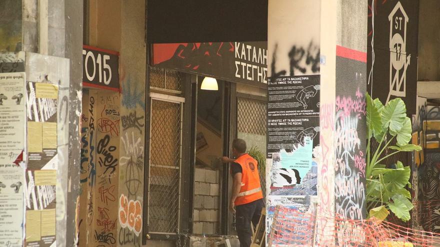 Una persona tapia la puerta de entrada al edificio ocupado Spirou Trikoupi 17 en el barrio de Exarjia.