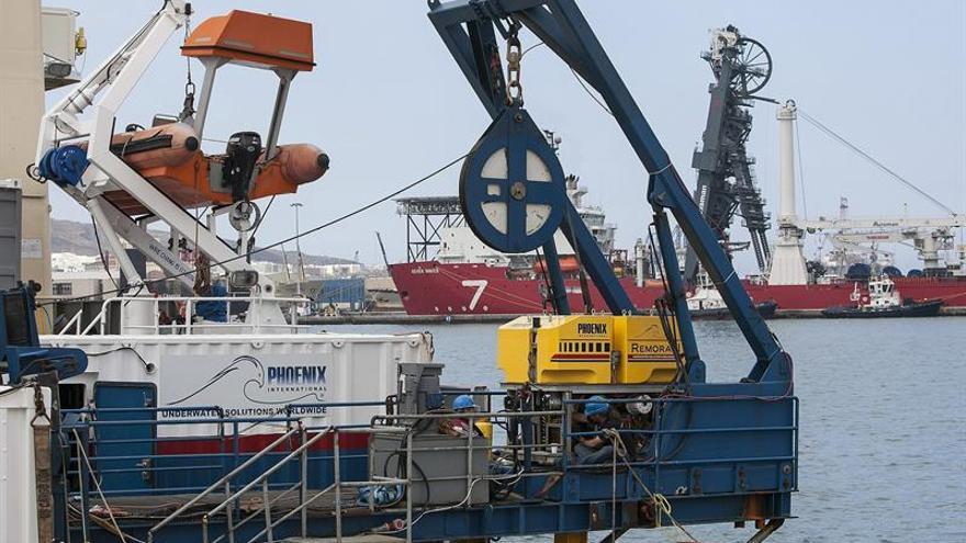El buque 'EDT Ares', de la compañía norteamericana Phoenix Internacional, en la Base Naval de la capital grancanaria, desde donde partirá a la zona donde cayó el helicóptero del SAR, que se estrelló en aguas de Canarias el pasado 19 de marzo, para incorporarse a las tareas de localización de este aparato. Esta embarcación cuenta con el vehículo operado de forma remota (ROV) Remora II (a la dcha. en la imagen) que será el encargado de sumergirse hasta localizar el helícoptero, para posteriormente intentar rescatar la aeronave siniestrada. EFE/Ángel Medina G.