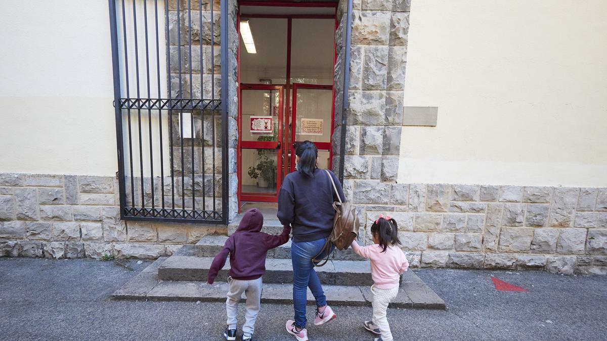 Una madre lleva a sus hijos al Colegio Público Víctor Pradera de Pamplona