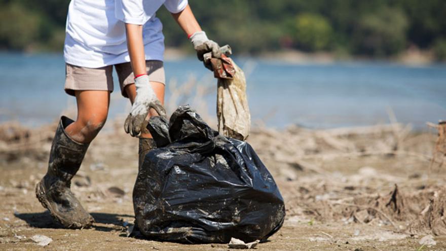 Una voluntaria limpia una playa.