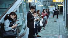 Personas mirando sus móviles en un andén de metro.