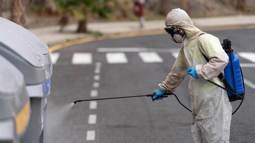 Personal del servicio de limpieza de la capital tinerfeña desinfecta la calle Nisamar del barrio de Añaza este viernes tras 20 días de la declaración del estado de alarma para frenar la expansión del coronavirus.