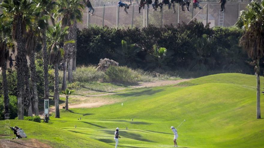 Unos diez inmigrantes, encaramados en la valla de Melilla frente al campo de golf situado al lado de la alambrada que separa la ciudad autónoma de Marruecos. / Foto: José Palazón / Prodein