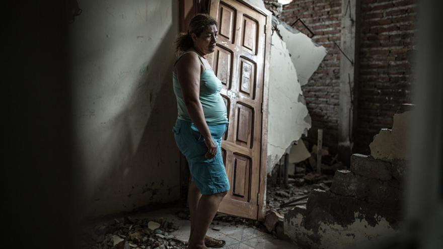 Alba observa lo que queda de su casa. La fachada se ve intacta pero adentro está totalmente destruída. Con ellos viven 3 hijos y una nieta de 2 años.   Pablo Tosco/Oxfam Intermon