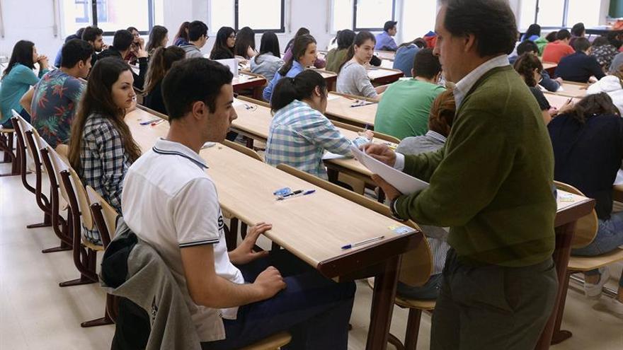 Un profesor reparte los exámenes a los estudiantes. Foto de archivo