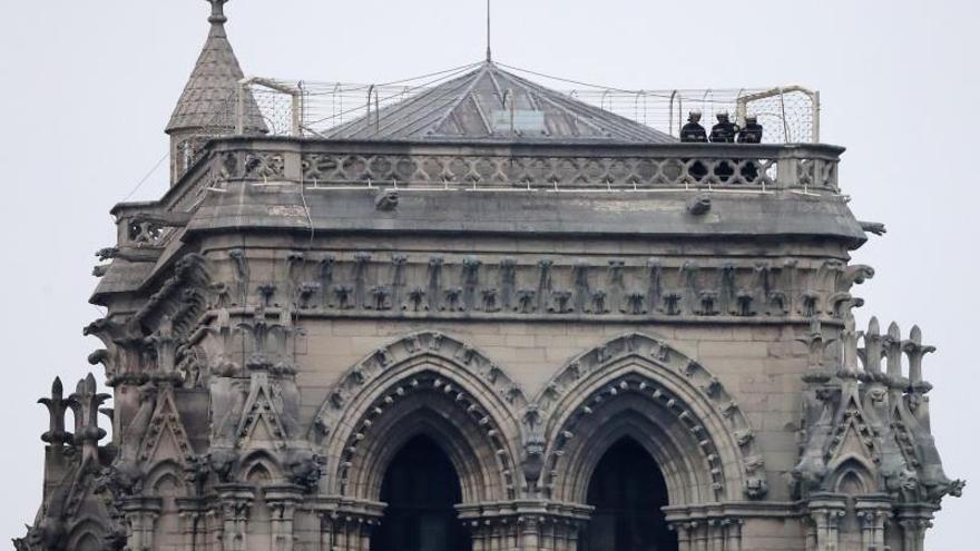 Varios bomberos trabajan, este martes, en lo alto de una de las torres principales de la catedral de Notre Dame, de París (Francia)