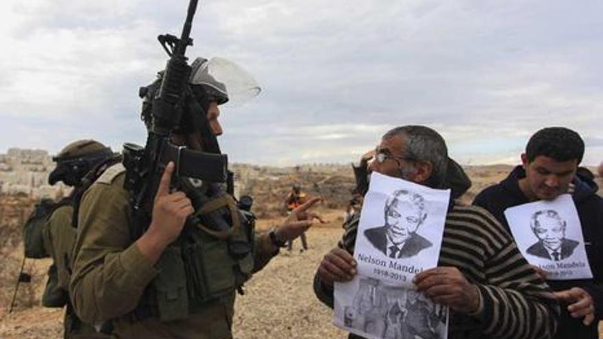 Palestinos muestran la foto de Mandela en la protesta semanal contra el muro de separación (Efe)