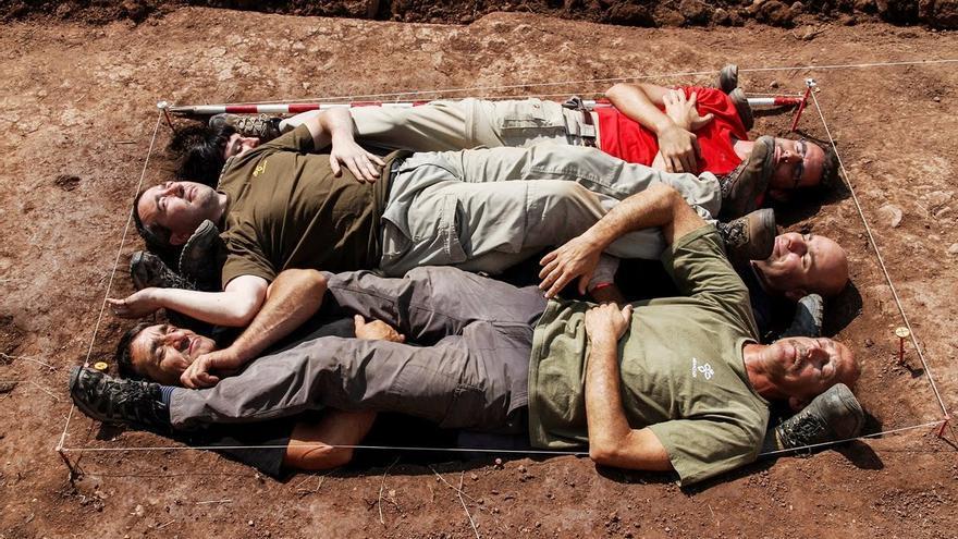 Ritual forense a pie de fosa: varias personas ocupan las huellas corpóreas de las personas exhumadas por el equipo de Aranzadi en esta fosa de en Barcones (Soria) en julio de 2013. Foto: Óscar Rodríguez / ARMH.