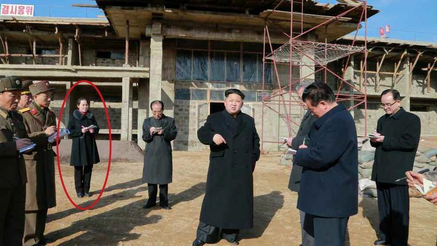 Kim Jong-un en primer plano, en una foto de 2015, con su hermana Yo-jong detrás, tomando notas.