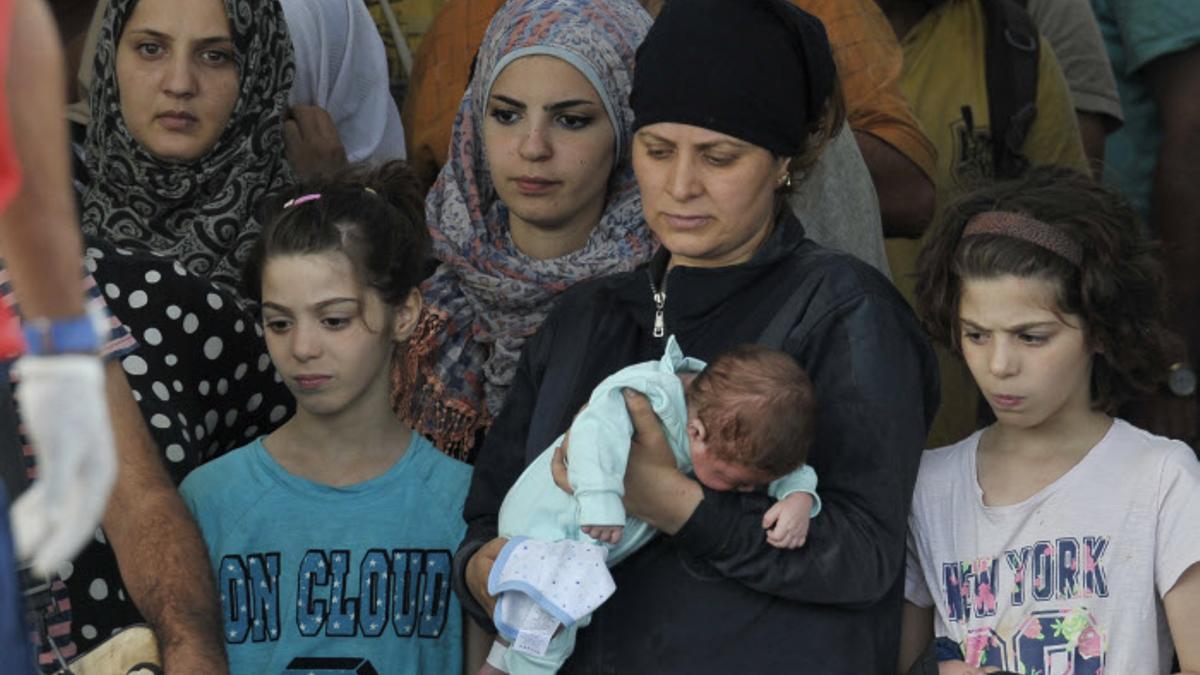 Migrantes esperan a desembarcar en el puerto de Augusta, en Sicilia.