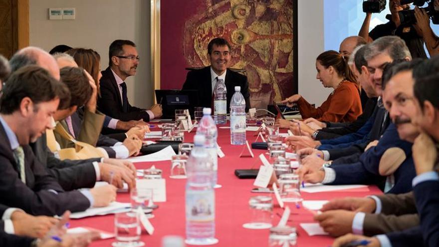 El presidente del Gobierno, Fernando Clavijo (c), durante la reunión que ha mantenido con los representantes de las federaciones canarias de islas y ayuntamientos, la Fecai y la Fecam. EFE/Ángel Medina G.