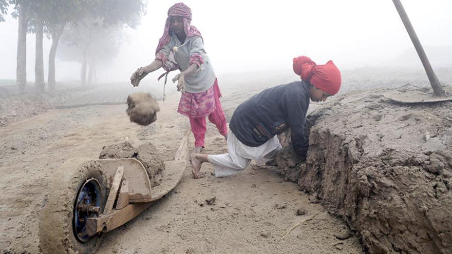 Rabia y su hermano Sidra son pakistaníes. Tienen 8 y 10 años. A pesar de que ambos estudian, deben ayudar en la economía familiar y por eso trabajan en la fabricación de materiales de construcción. Sin zapatos, sin acceso a un baño, sin agua potable y sin tener un descanso. Sólo comen una vez al día. (Umar Farooq/ActionAid)