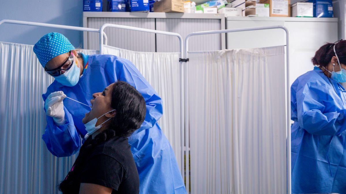 Un trabajador sanitario protegido le realiza a una mujer un test PCR