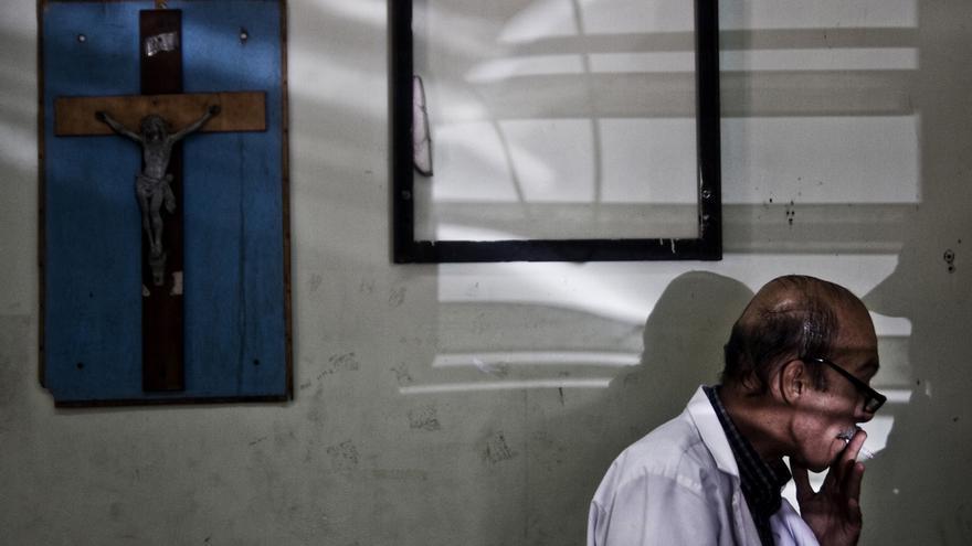 El doctor Eduardo Abullarade fuma un cigarrillo en la morgue del Hospital Rosales, en San Salvador. Él era uno de los 139 forenses que trabajaban en el Instituto de Medicina Legal de El Salvador./Edu Ponces (RUIDO Photo)