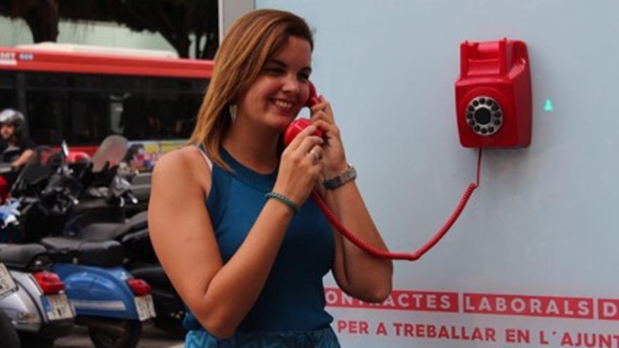 La regidora Sandra Gómez amb el telèfon que publicita un programa d'ocupació de l'Ajuntament de València.