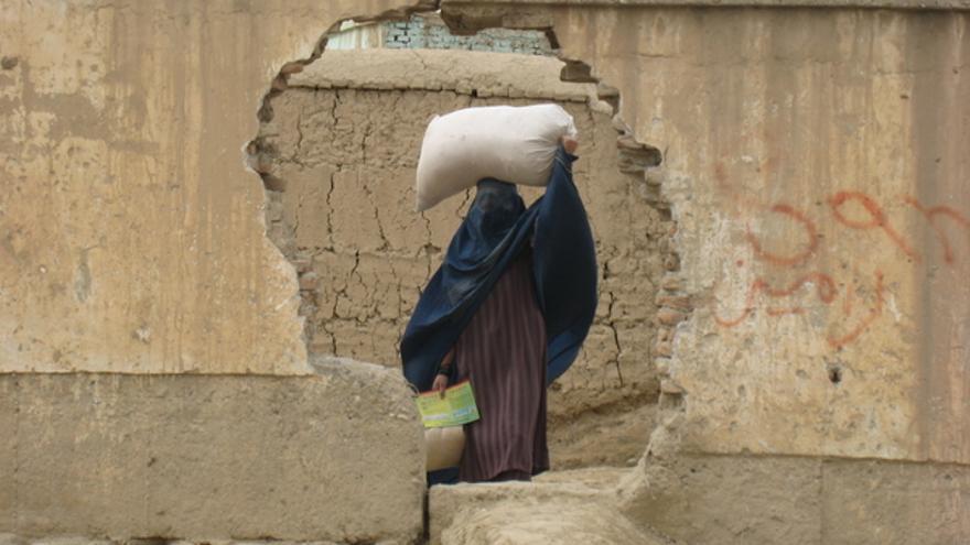 Una mujer camina llevando un saco en la cabeza en los barrios marginales de Mazar-e-Sharif, Afganistán, 23 de febrero de 2010 © AI