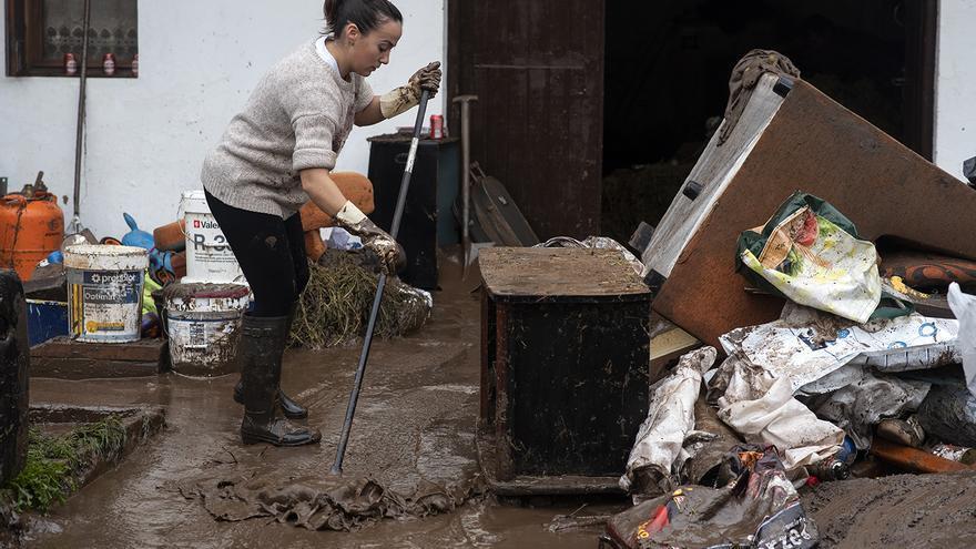Una afectada por las inundaciones en Cantabria trata de sacar el agua de su vivienda. | JOAQUÍN GÓMEZ SASTRE