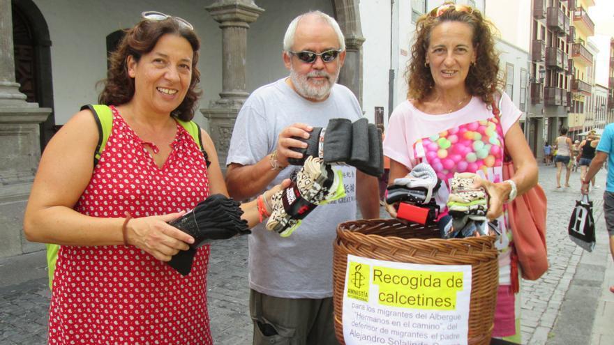 En la imagen, tres ciudadanos, este sábado, donando calcetines para los migrantes. Foto: LUZ RODRÍGUEZ
